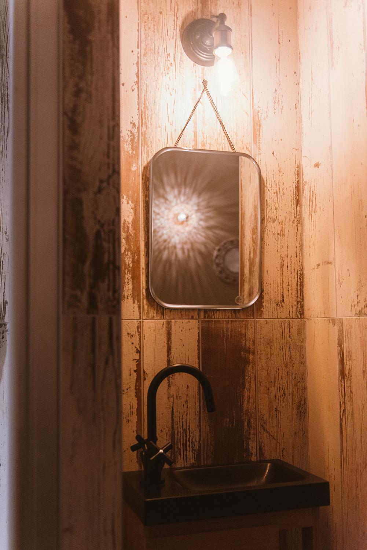 Espace lavabo dans une salle de massage du spa, avec miroir et luminaire au design vintage